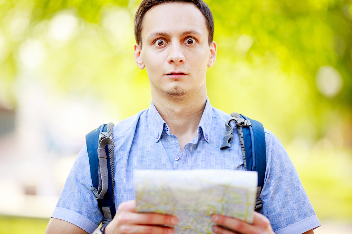 Lost tourist holding map in hands and looking at camera