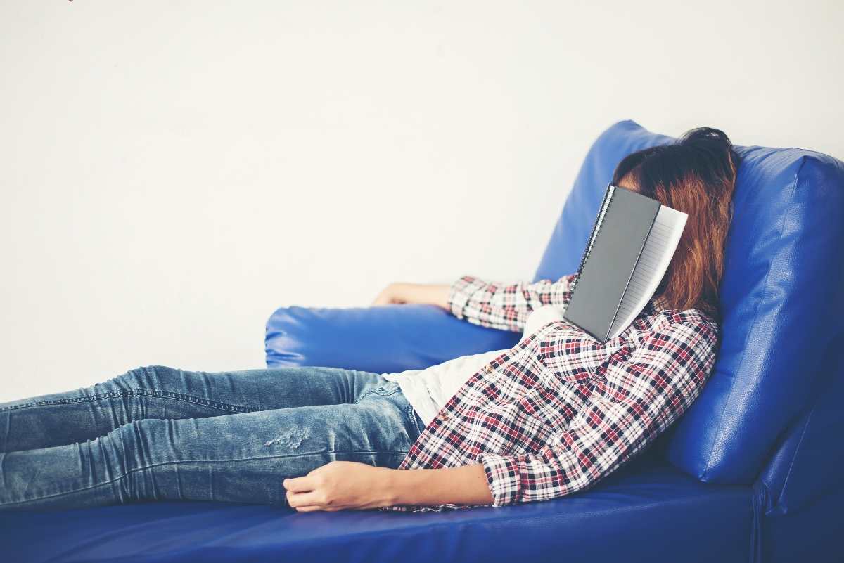 Young beautiful woman sleeping on blue sofa tired for writing.