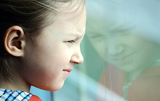 Thoughtful little girl looking into window