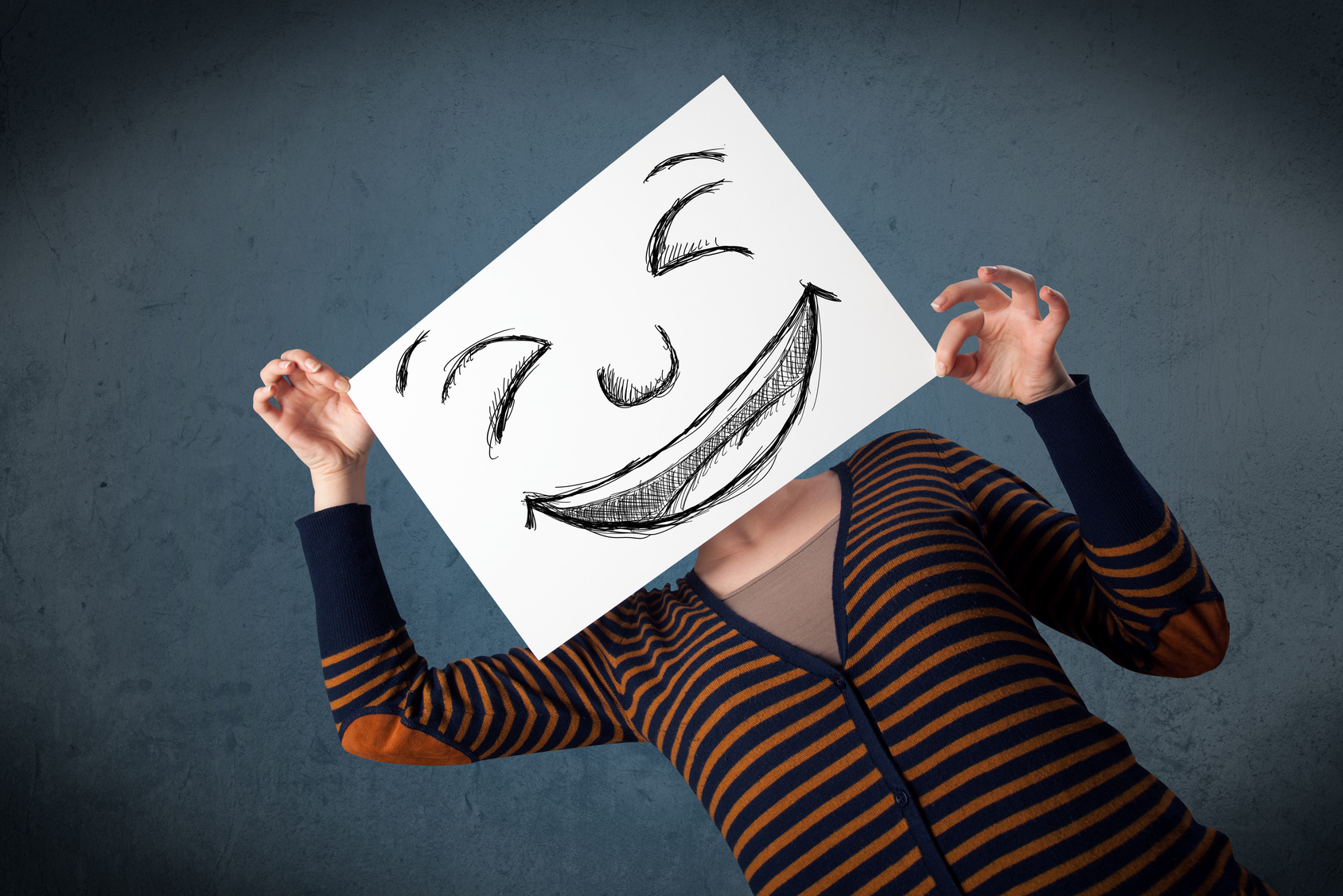 Woman with drawed smiley face on a paper in front of her head