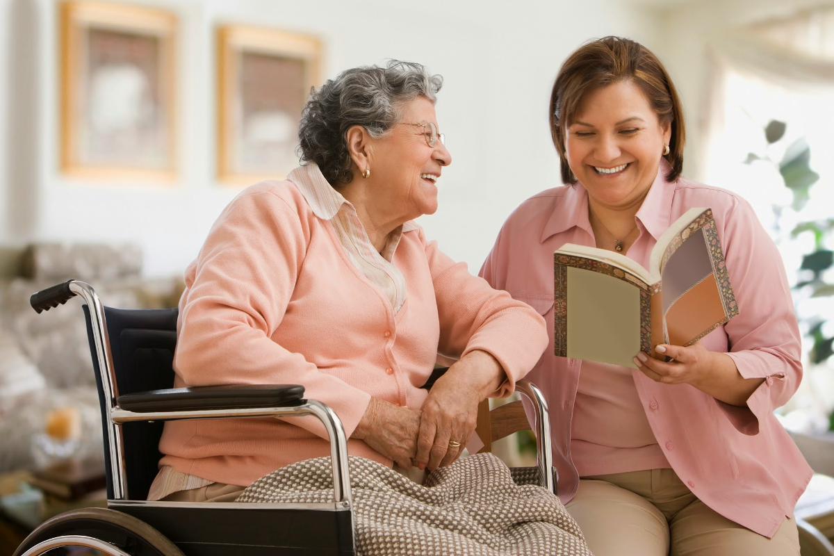 Hispanic woman reading to mother
