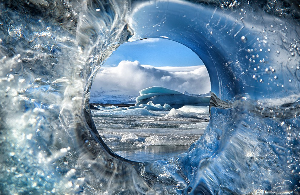 PIC BY TIM VOLLMER / CATERS NEWS - These incredible images capture the ever-changing beauty of the worlds glistening glaciers - from being shrouded in volcanic ash to gracefully disappearing into the sea.Ice man Tim Vollmer, 41, has spent years snapping the magnificent changing appearance of icebergs and glaciers to create his breath-taking catalogue of shots.He has braved freezing temperatures to photograph icebergs as they create a dazzling display of colour when the time comes for them to melt and disappear.And hes even travelled to capture the moment the usually crystal clear ice was turned black back in 2010 during the Eyjafjallajokull volcano eruption.SEE CATERS COPY