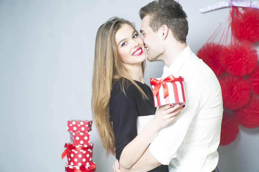 Romantic couple of young people embraces and standing close to each other holding gift, horizontal photo