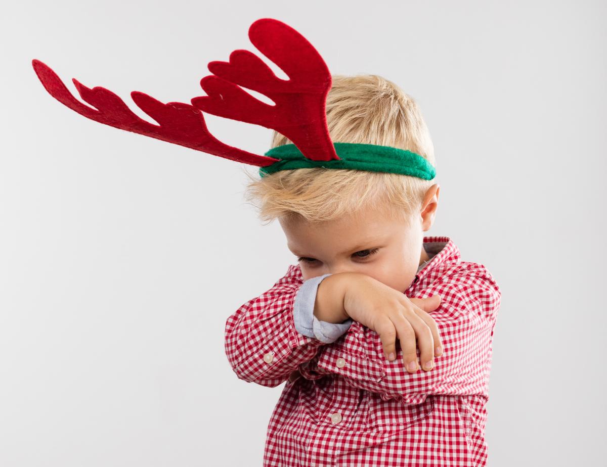 Christmas scene. angry boy with reindeer antlers
