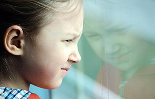 Thoughtful little girl looking into window