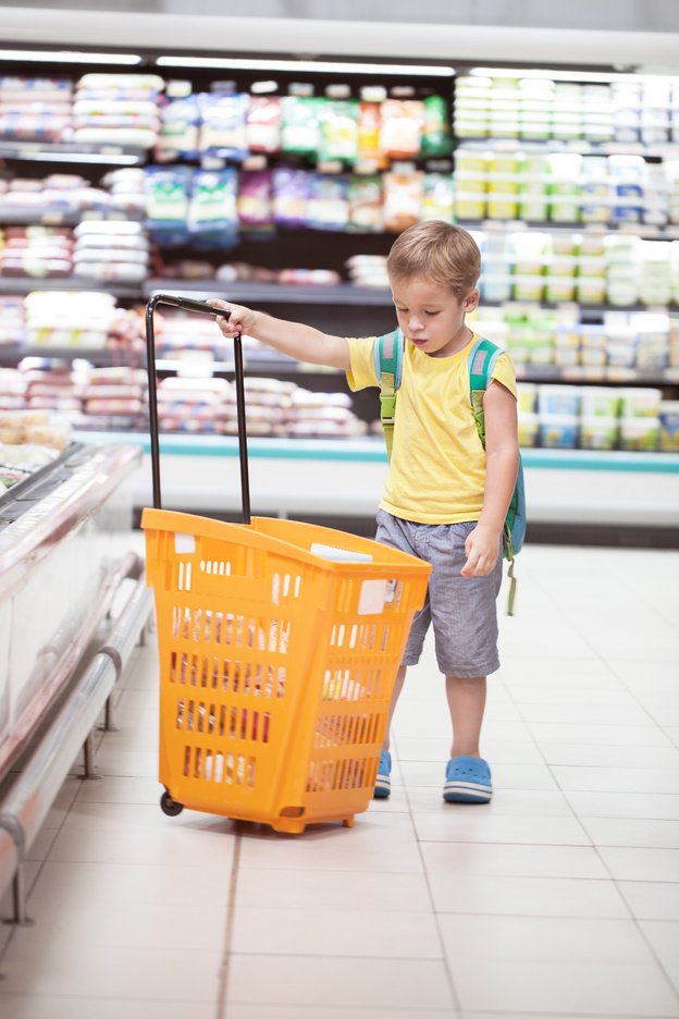 Little boy in the supermarket looking at big full shopping cart. Child going shopping alone