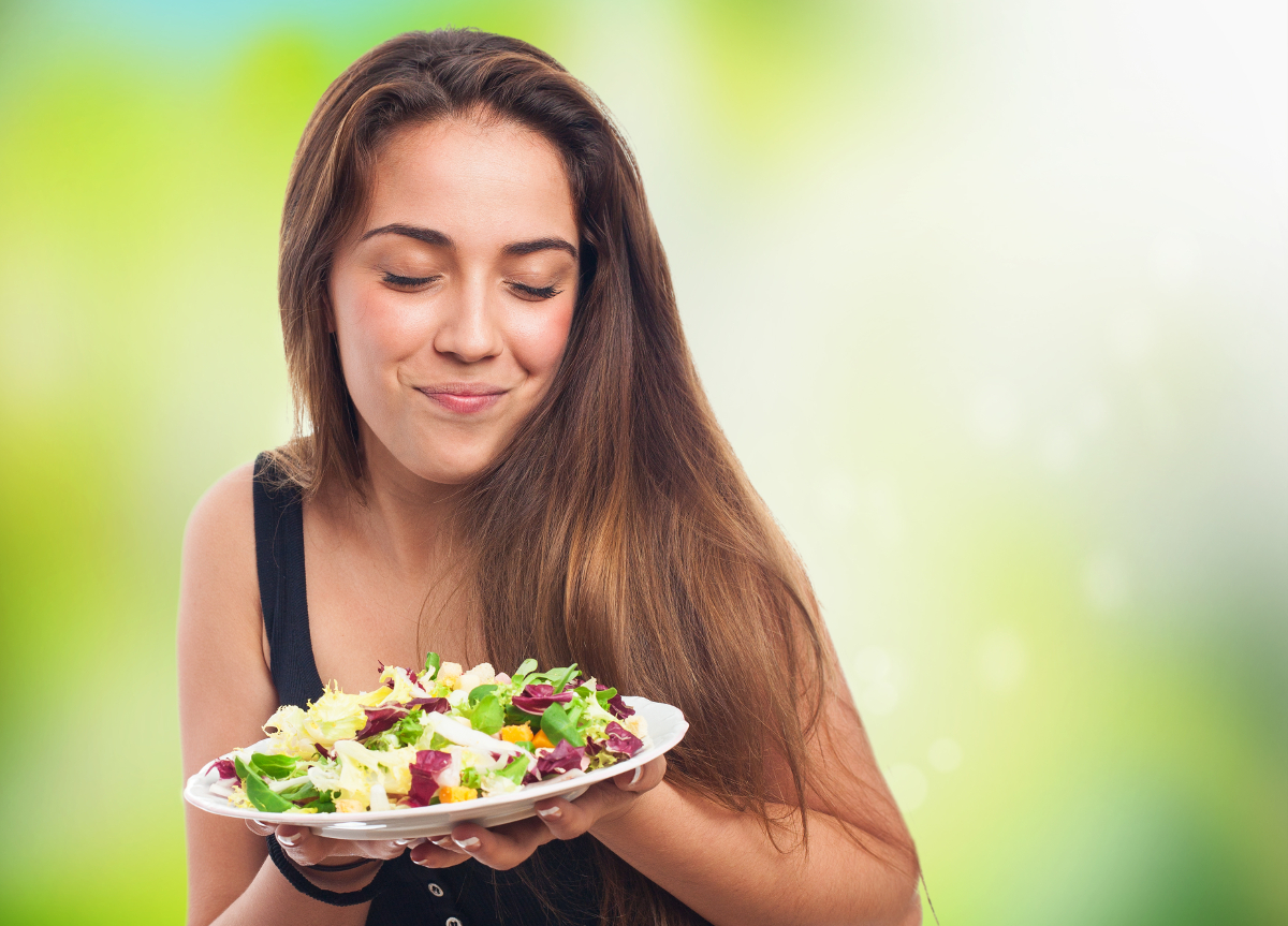 portrait of a woman holding a delicious salad